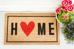 Doormat that says Home with a red heart and flowers to the right of it.