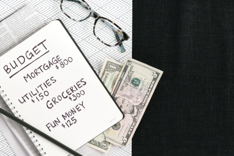 Notebook with budget information with glasses, 5 dollar bill and 1 dollar bill on a black background.