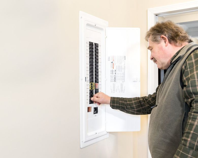 man checking circuit breakers