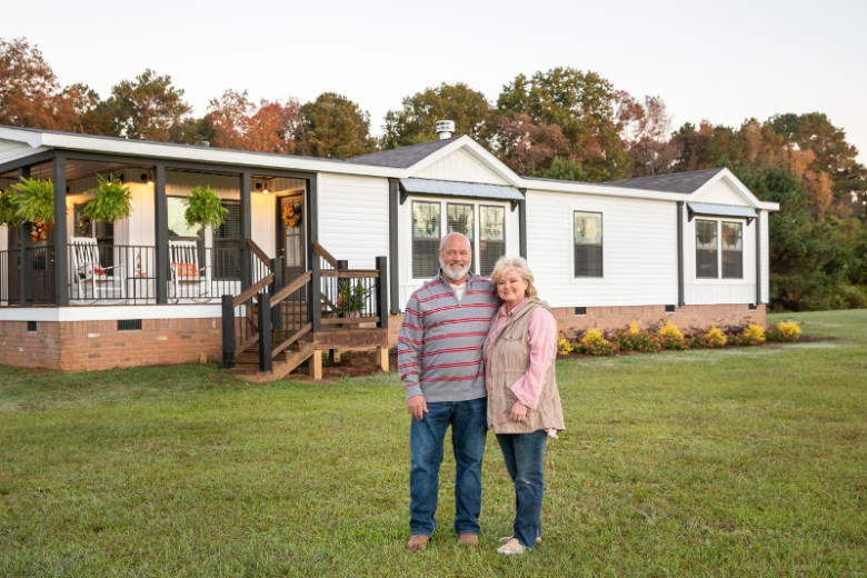 Couple stands in front of their manufactured home that has a farmhouse theme.