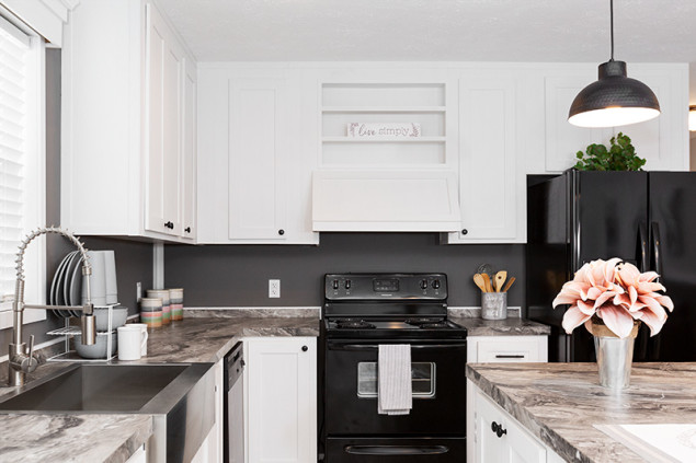 A manufactured home kitchen with white cabinets and stone style counter tops.