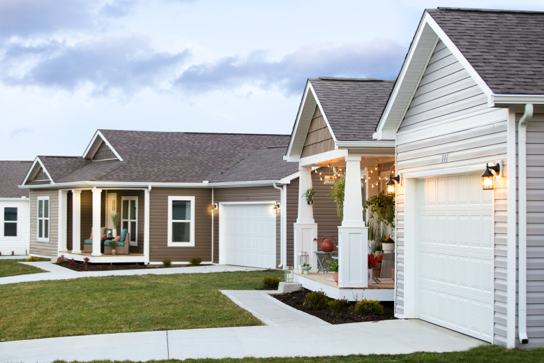 A new class of manufactured homes in a neighborhood with garages.
