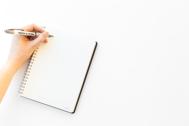 A blank notebook on a white background with a hand about to write something.
