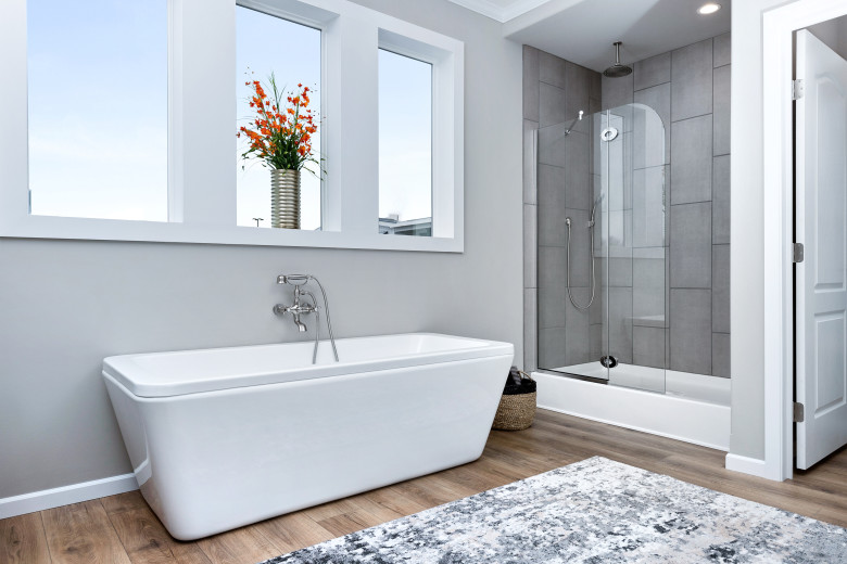 Rectangular garden tub placed under 3 windows and beside a large walk in shower of a manufactured home bathroom