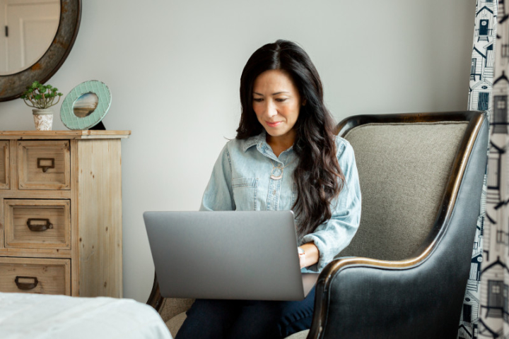 Woman with long, dark hair uses a laptop in a bedroom with light wood dresser and patterned curtains.