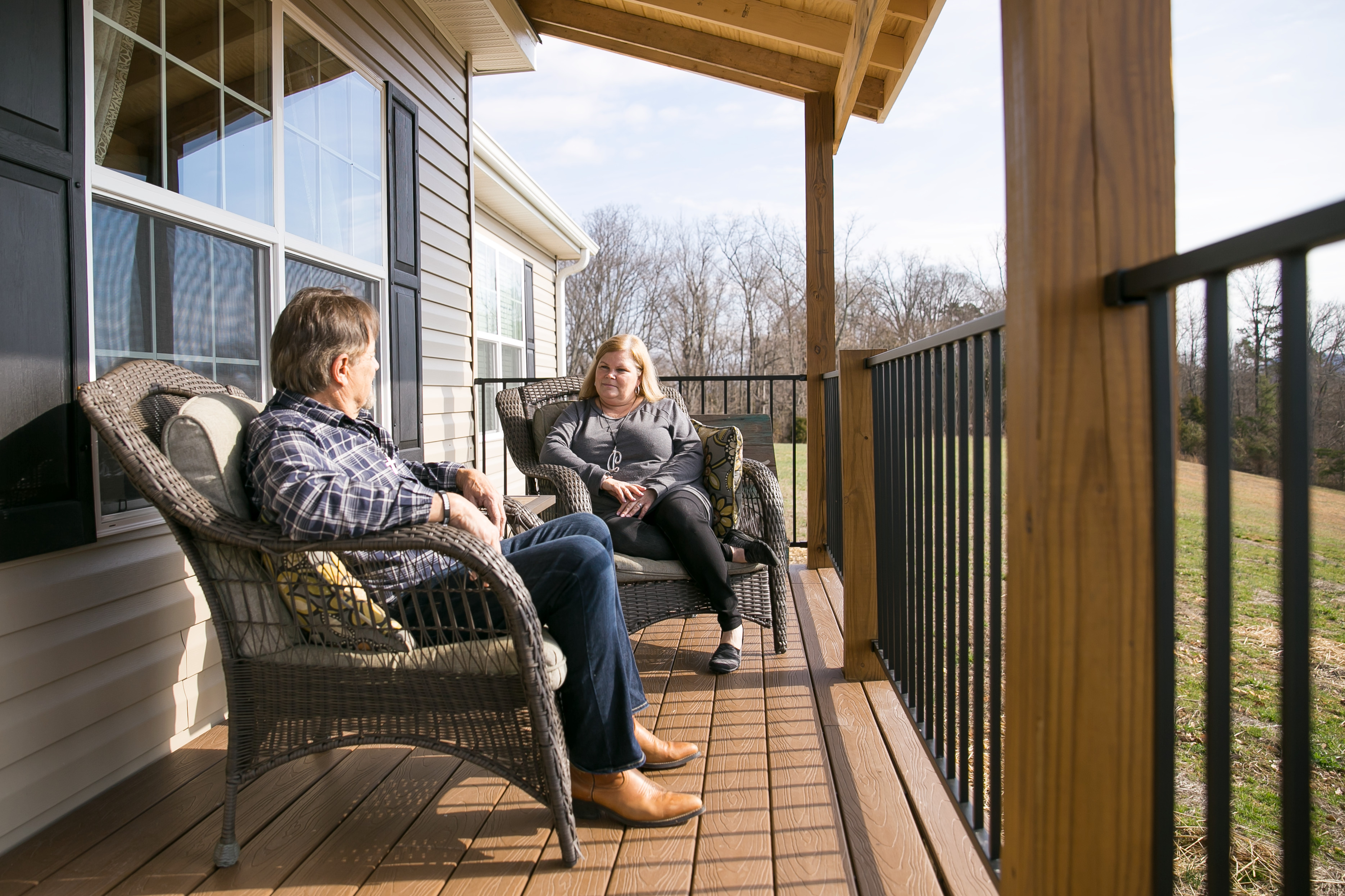 Couple sitting on their manufactured home porch together