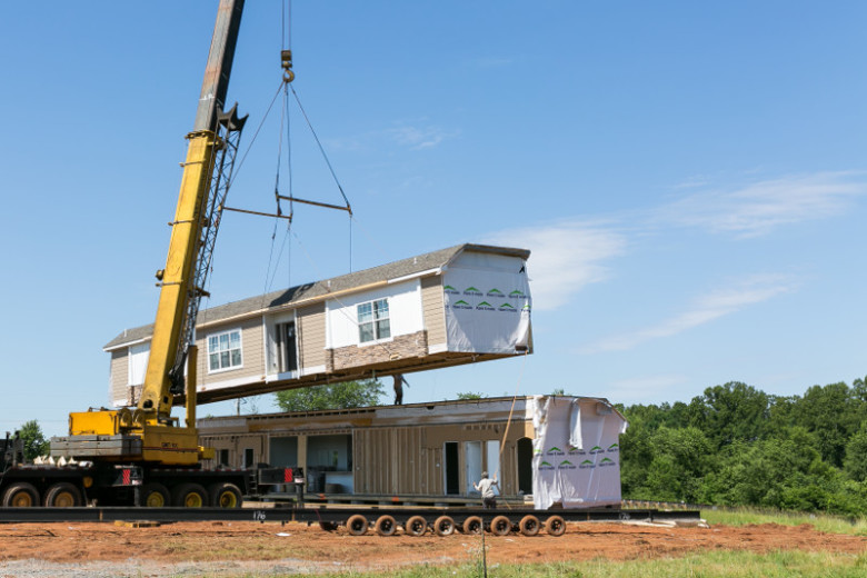 Crane setting up double-wide modular home at a home site.