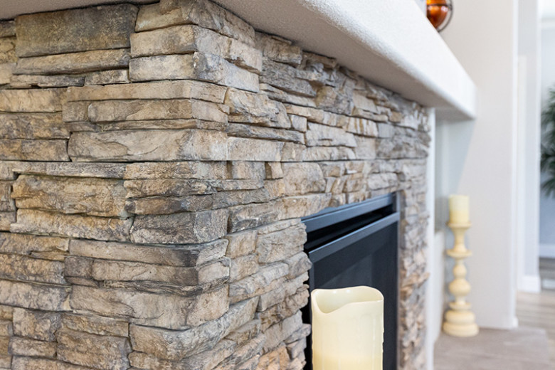 Closeup of light brown and gray stone fireplace with white mantel and 2 cream candles on the hearth.