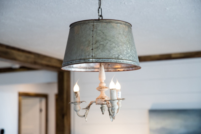 Two round, galvanized metal pendant lights handing from a white ceiling.