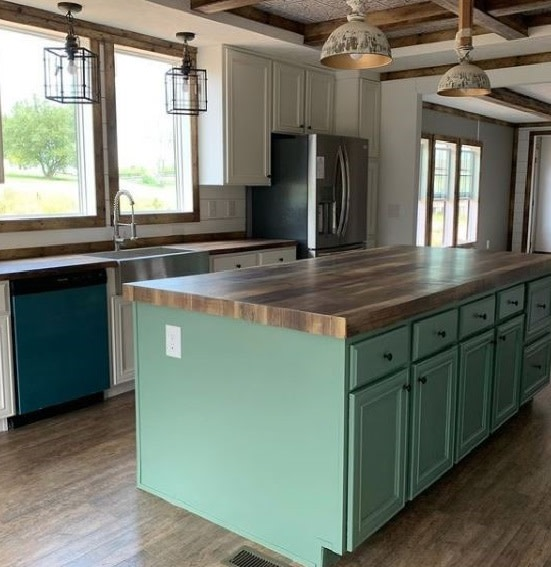 Manufactured home kitchen with white cabinets and a teal island with wooden counters.
