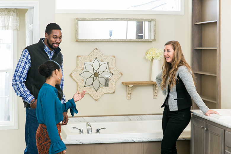 Couple and female home consultant stand in the primary bathroom of a manufactured home with window above the bathtub, shelves built in next to tub and vanity in beige colors.