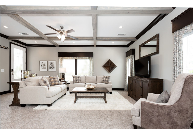 Manufactured home living room with gray stained coffered ceilings and beige carpet.