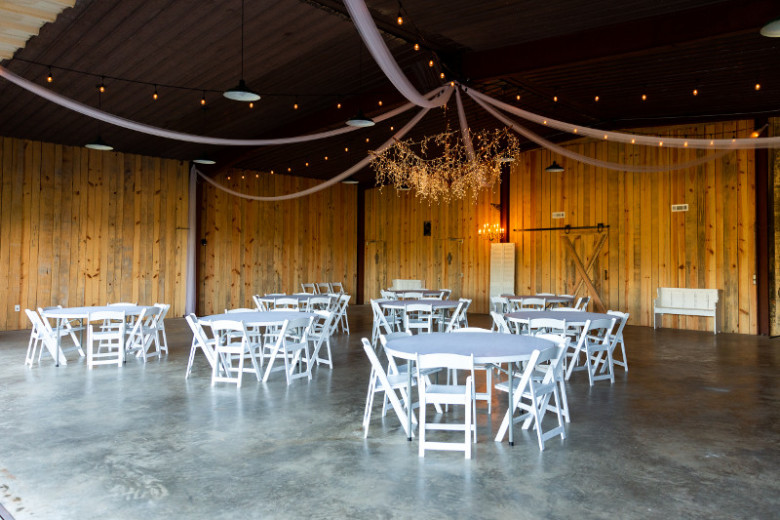 The inside of a wedding venue showcasing white chairs and tables.