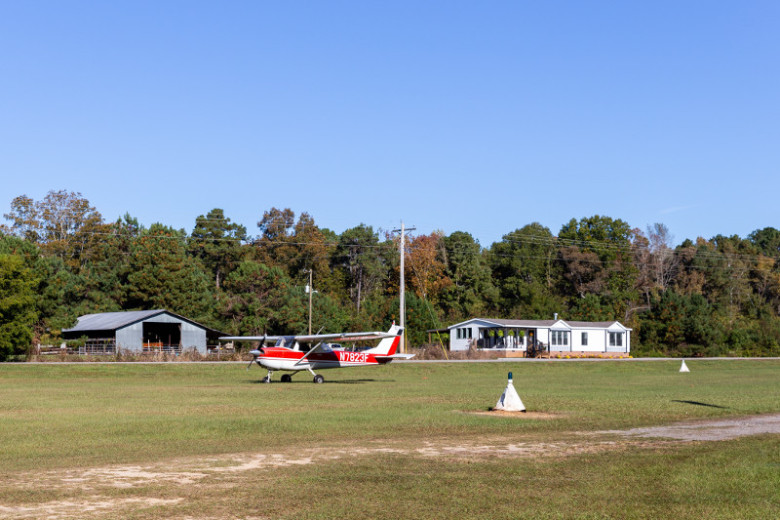 Red airplane on runway in front of manufactured home.