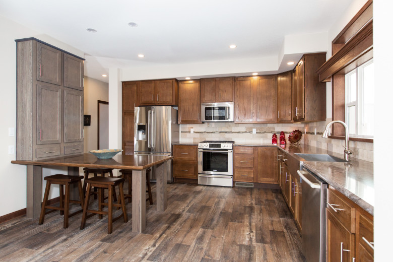 Manufactured home kitchen with wooden cabinetry.