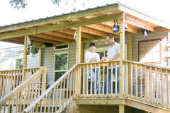 Woman and man stand on the wooden porch of their manufactured home with light gray siding, with wooden stairs.
