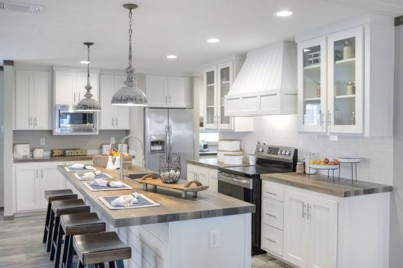 You don't have to look hard to find beautiful, unique features in The Littlefield kitchen like wood style countertops, glass door cabinets, a range hood and subway tile backsplash.