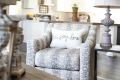 Gray toned chair with white pillow that says 'let's stay home' in gray lettering.