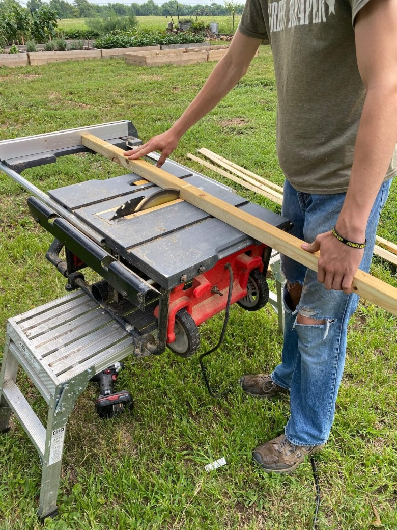 Man cutting 2X2 boards in the garden of a manufactured home.