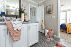 Primary bathroom of a manufactured home with white vanity with gray counters with toiletries, flowers and towels, with a door leading to the hallway and a door to the bedroom.