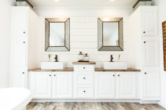 Manufactured home master bathroom with double sinks and white cabinetry.
