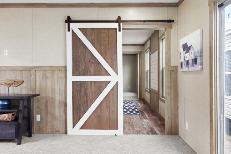 Sliding barndoor on a tan wall with wood paneling.