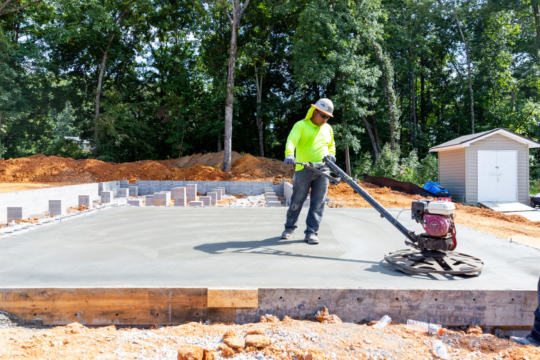 Man laying foundation for a manufactured home.
