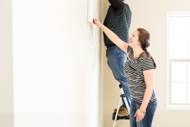 Man and woman painting walls in a manufactured home.