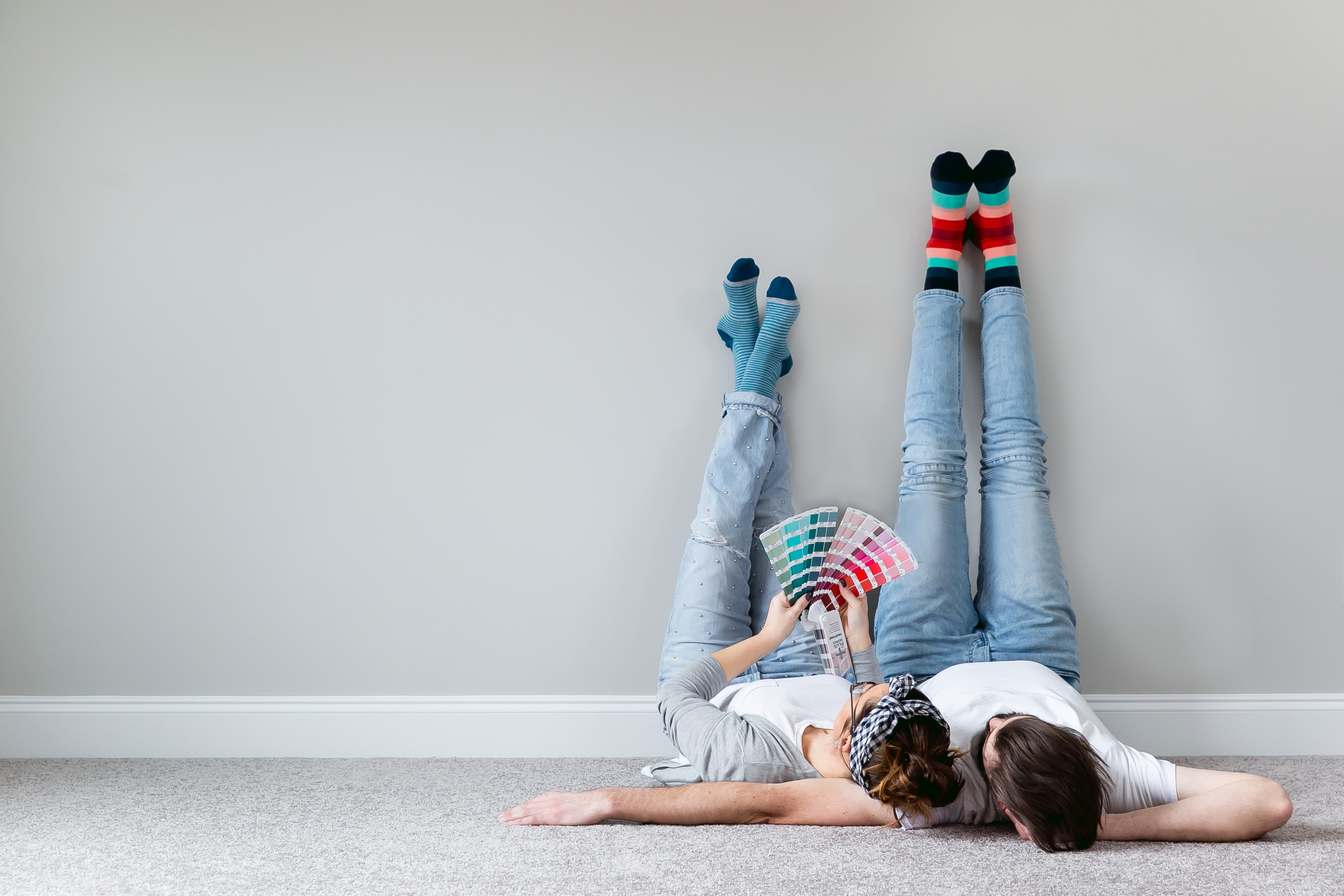 Couple laying on the floor with crazy socks looking through paint colors on a fan deck in their manufactured home