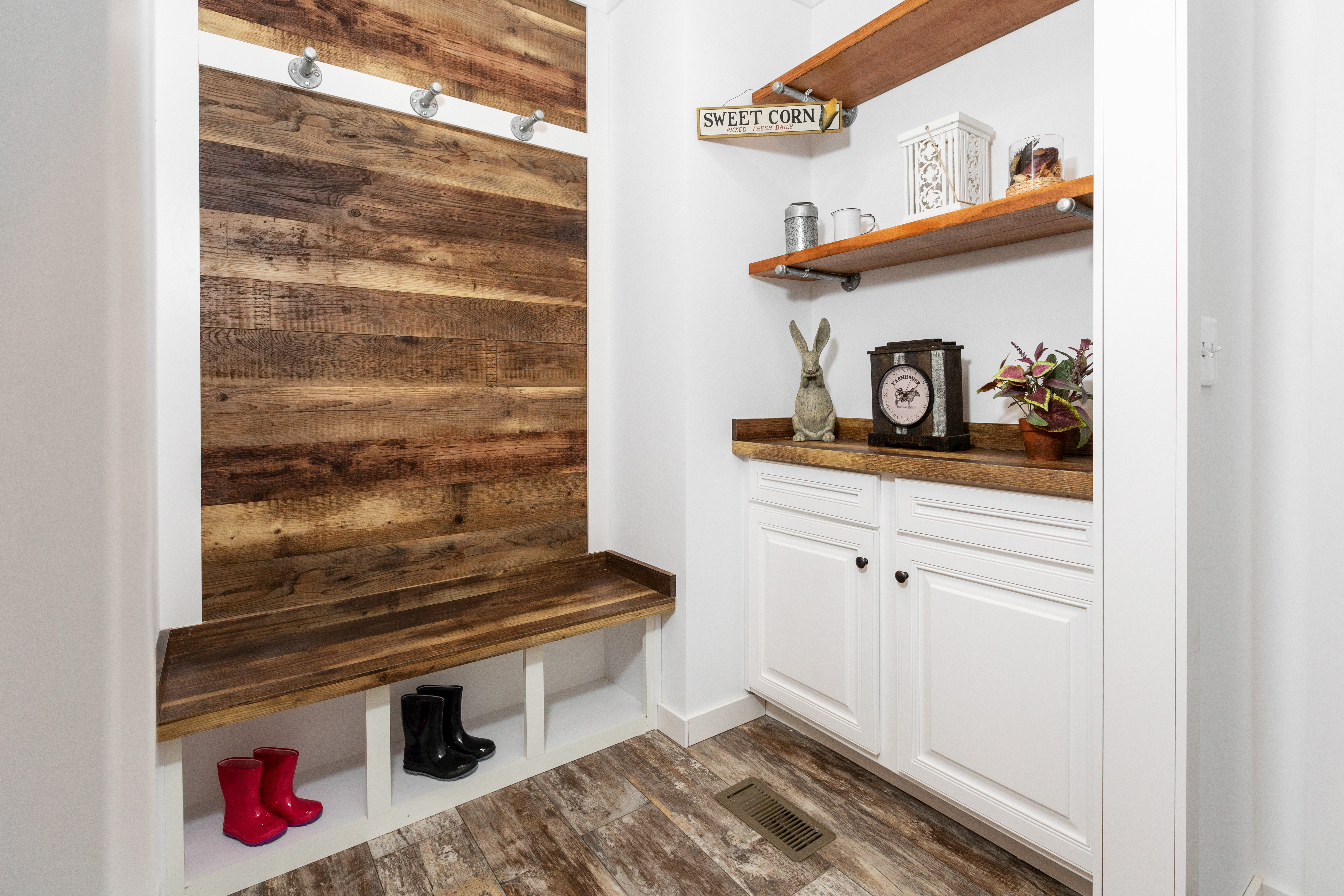 Mobile home mudroom with dark wood accent and custom shelving.