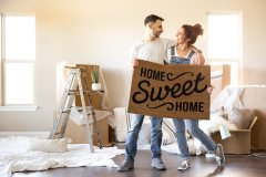 "Young couple holding a ""home sweet home"" welcome mat in their new manufactured home."