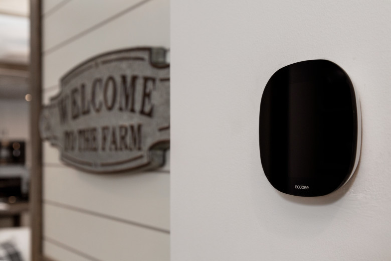 ecobee thermostat hanging on the wall next to shiplap features in a manufactured home.
