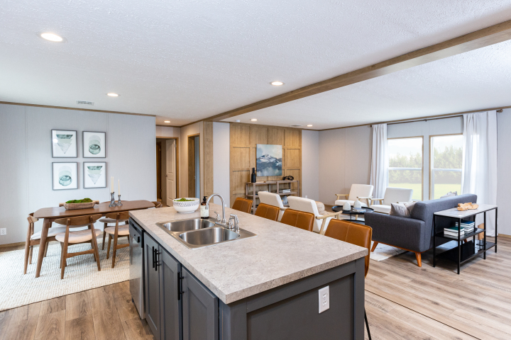 The Rio by Clayton is part of the manufactured home Adventure Series, featuring an open layout with a long kitchen island and an accent wall in the living room.
