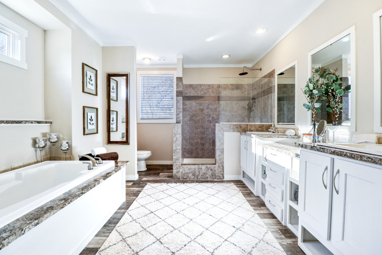 A beautiful manufacture home bathroom with a soaker tub, walk-in tile shower, dual vanity and tons of white cabinet storage.