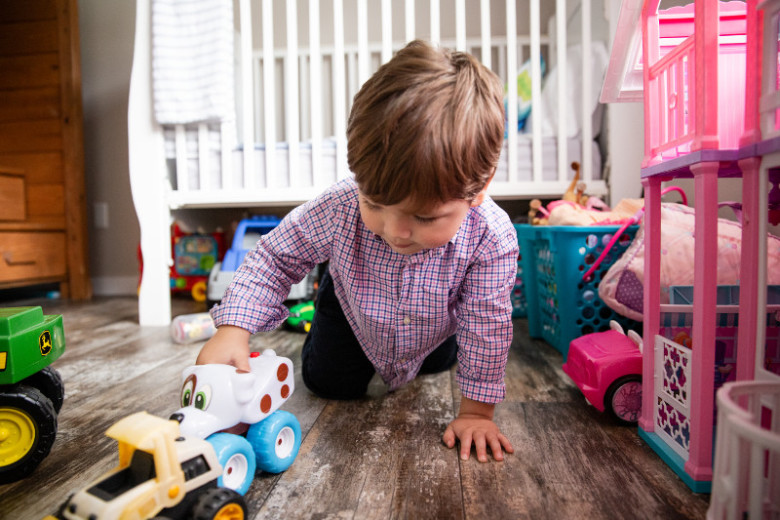 Child plays with toys on manufactured home floor.