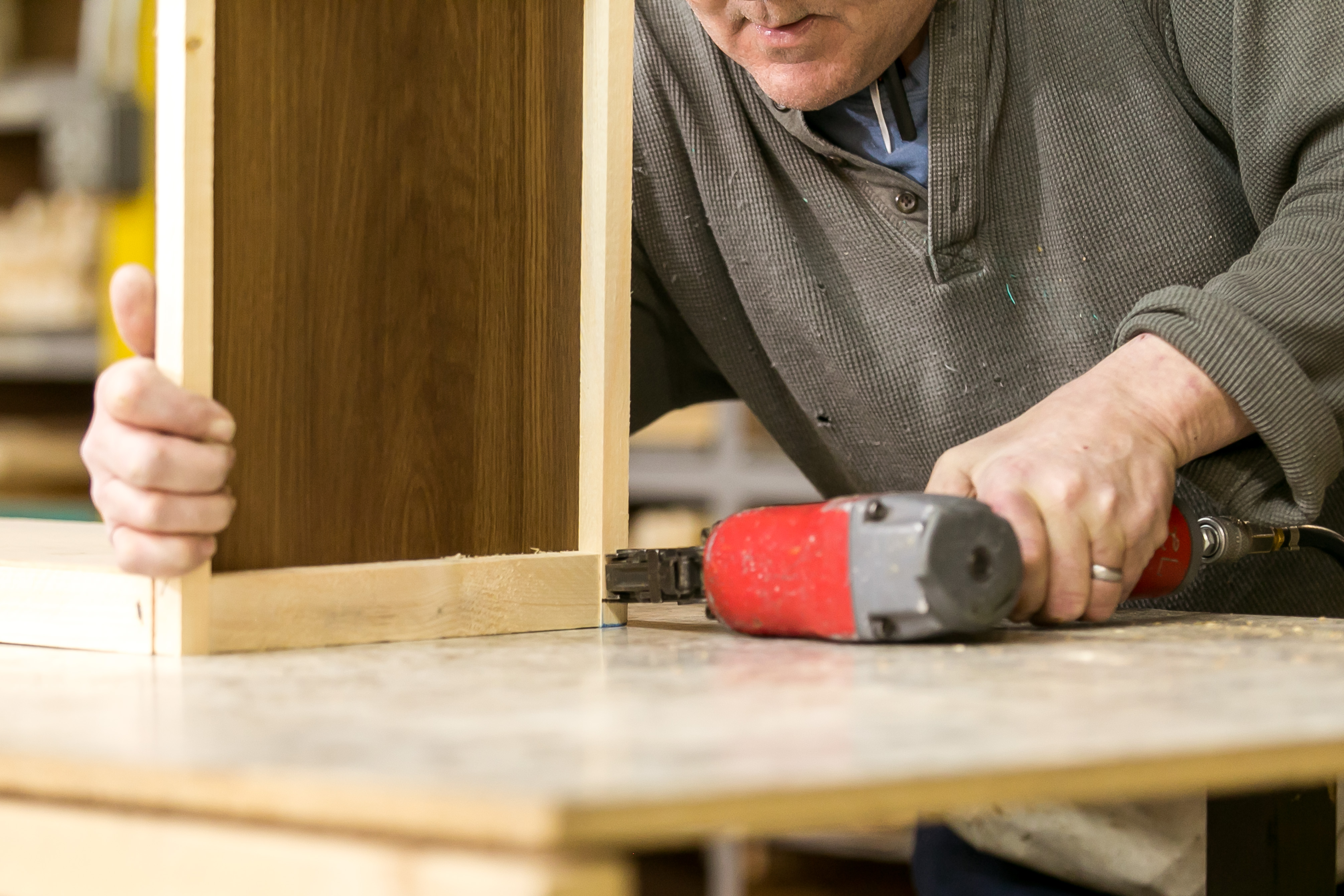 Team member works on assembling wood cabinets for a manufactured home.