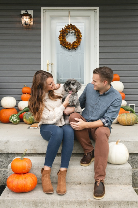 Couple sitting on porch of manufactured home with fall pumpkin décor.