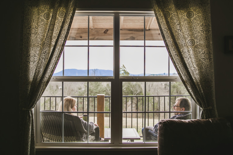 Husband and wife sit on their front porch looking out at the mountains