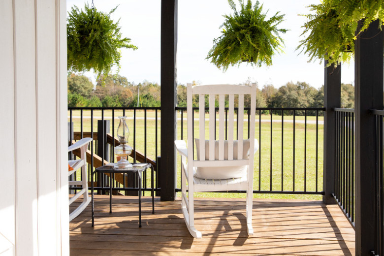 White rocking chair on a manufactured home covered porch looking over the homeowner's property.
