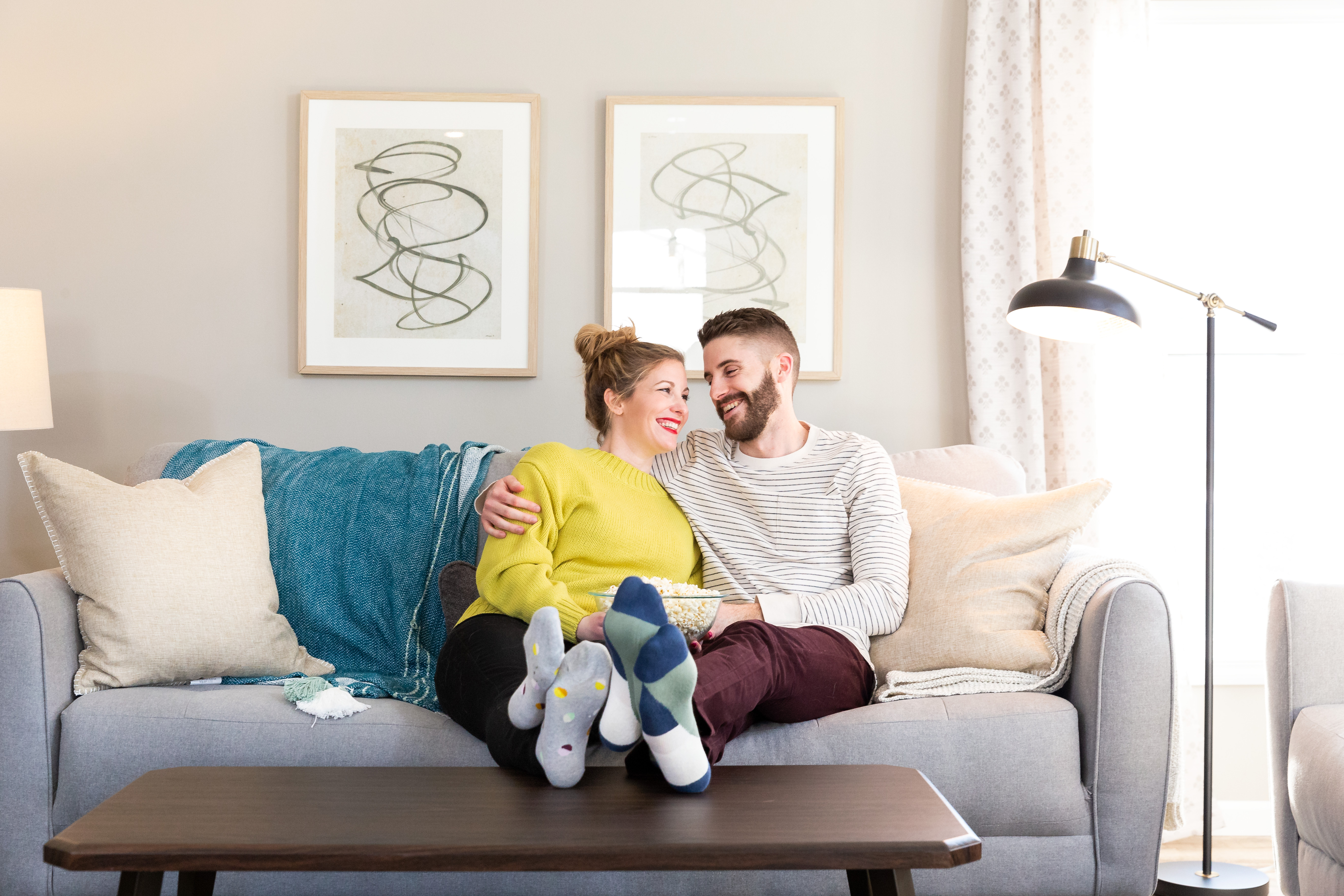 Couple cuddled up on a couch in their manufactured home living room