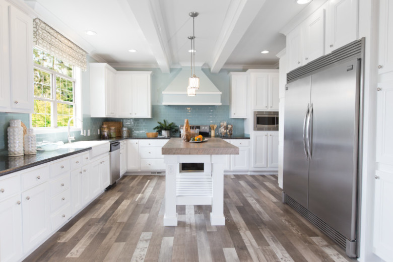 Contemporary kitchen in The St. Croix manufactured home with white cabinets, light blue backsplash and stainless steel appliances.