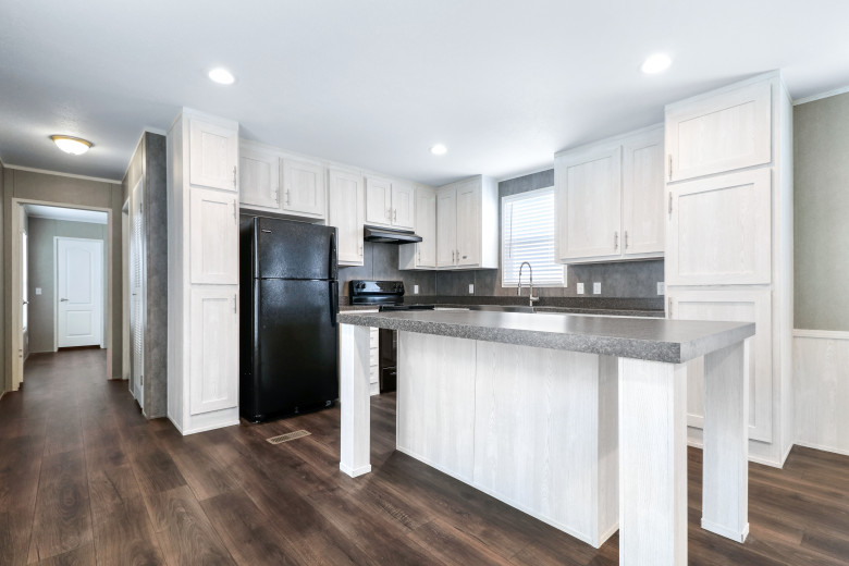 Manufactured home kitchen with white cabinetry and a large breakfast bar.