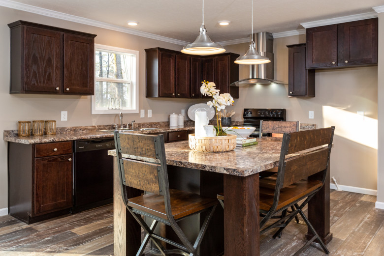 Manufactured home kitchen with dark wooden cabinetry and a large breakfast bar.