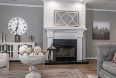 The living room of The Abigail by SouthernEnergy featuring a fireplace with a surrounding white wood mantle and a black stone hearth.