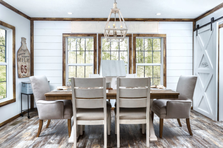Dining room of a manufactured home featuring shiplap walls, wood trim, 3 windows, chandelier, wooden table, beige chairs and white sliding barn door.
