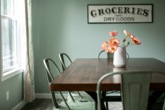 Dining room area with dark wood table, sage green colored metal chairs and a flower center piece.