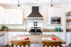 The kitchen of the Southern Charm home model, featuring a range hood, stainless steel appliances and an island.