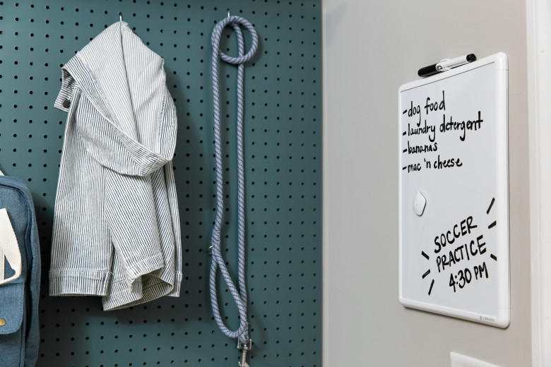 Green pegboard with jacket and dog leash hanging on the wall next to a white board