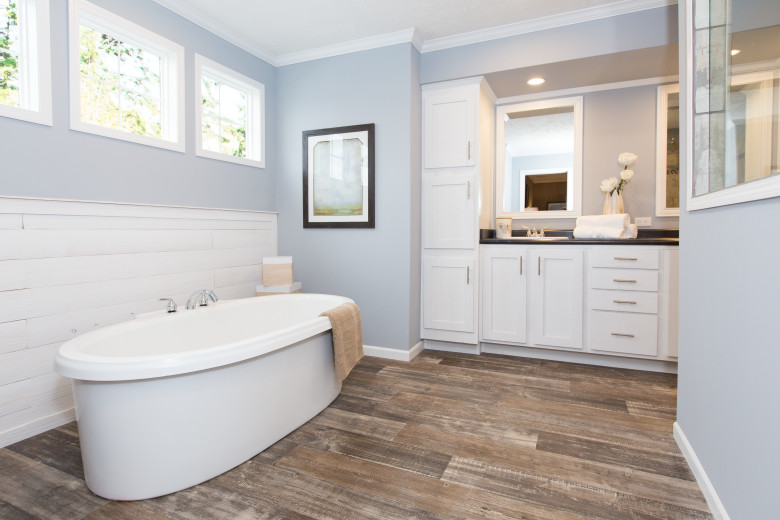 Primary bathroom of the Churchill with light gray painted walls and a freestanding soaker tub.
