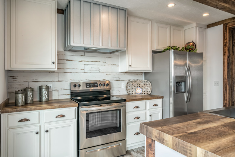 Kitchen of the Avalyn displaying white cabinets and wooden countertops.